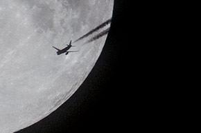 Supermaan met passerend vliegtuig.